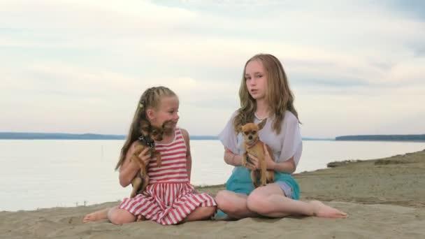 Dvě děti bruslit, seděl na písku na pláži