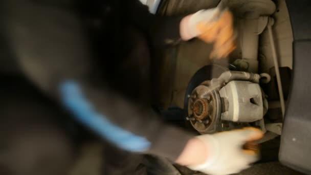 Auto mechanik pracuje na brzdy v garáži domácí obchod opravy aut.