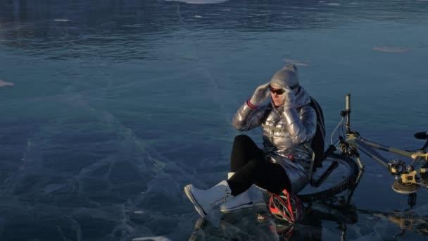 Žena je jízda kole na ledě. Dívka je oblečená v stříbřitě péřová bunda, Cyklistika helma a batoh. Cyklista se zastavil na odpočinek. Ona sedí na kole a částečně sundá šaty