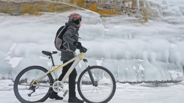 Man is walking beside bicycle near the ice grotto. The rock with ice caves and icicles is very beautiful. The cyclist is dressed in gray down jacket, backpack and helmet. The traveler is ride cycle.