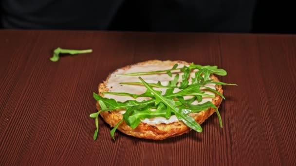 Burger főzés a fekete háttér. Nagyon zamatos levegő zsemle és a márványos marha. Étterem, ahol minden hamburgert főtt kézzel. Sült saláta kitûnõ fektetni bun. Nem készült ideális. Úgy néz ki, igazi, szerető kézzel készített.