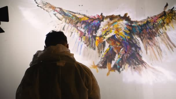 Artist designer draws an eagle on the wall. Craftsman decorator paints a picture with acrylic oil color. Slow motion 180fps.