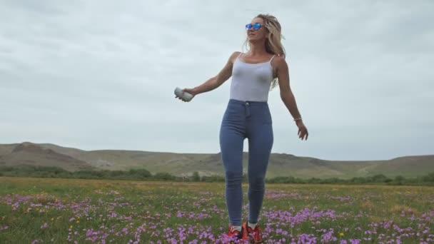 Kamera sledovat hipster mladá žena v bílém tričku krátké džíny třepetající se dlouhé vlasy. Jedna dívka tančí na přenosné hudební reproduktor na smartphone.