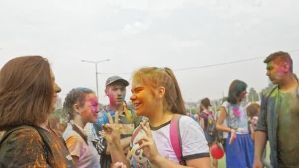 Rusko, Irkutsk - 27 června 2018: Happy mladých lidí tančí a slaví během Holi Festival barev. Dav lidí barevný prášek a baví v aréně.