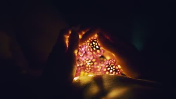 Kouzelné horké světlo luceren padá na ženské oči. Nahá dospělá sexy běloška leží v noci na posteli a drží v ruce teplé lampy.
