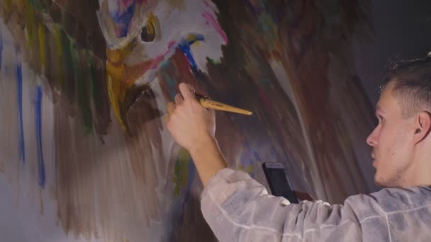 Artist designer draws an eagle on the wall. Craftsman decorator paints a picture with acrylic oil color looking at the sketch in the phone.