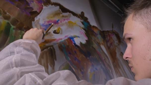 Künstler-Designer zeichnet einen Adler an die Wand. Handwerker Dekorateur malt ein Bild mit Acryl-Ölfarbe. Maler im Maleranzug.
