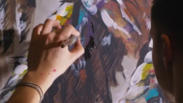 Umělec kreslí orla na zeď. Řemeslník dekoratér maluje obrázek akrylovou barvou oleje. Detailní záběr temné magie filmový vzhled.