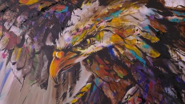A művész tervező egy sast rajzol a falra. Kézműves dekorátor festi a képet akril olaj színe. Festő festő festett kabát.