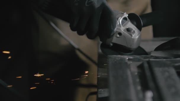 Schmiedewerkstatt. Behandlung Fertigprodukt. Nahaufnahme Details von Funken, Industriearbeiter mit Winkelschleifer und Schneiden von Stahl.