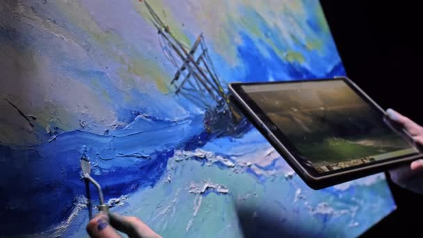 Artist copyist paint seascape with ship in ocean. Craftsman decorator draw as boat sail on blue sea with acrylic color. In hand of tablet computer pc.