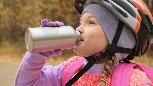 Kid drink water from an aluminum flask. One caucasian children rides bike road in autumn park. Little girl riding black orange mtb cycle in forest. Biker motion ride with backpack and helmet.