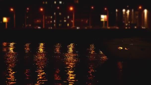 Luxusní moderní soukromá jachta a loď v noci na molu. Loď proplouvá v létě obzorem přístavu. Barevná světla záře města.