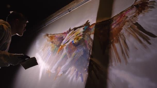 Künstler-Designer zeichnet einen Adler an die Wand. Handwerker Dekorateur malt ein Bild mit Acryl-Ölfarbe Blick auf die Skizze im Telefon.