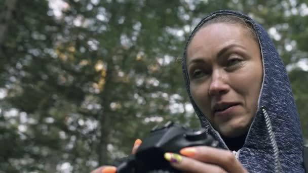 Utazó fényképezés festői kilátás az erdőben. Egy kaukázusi nő közelről lő. Lány fotózni videó dslr tükör nélküli fényképezőgép.