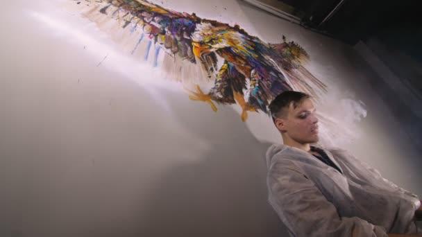 Künstler-Designer zeichnet einen Adler an die Wand. Handwerker Dekorateur malt ein Bild mit Acryl-Ölfarbe. Dampf raucht Dampf.
