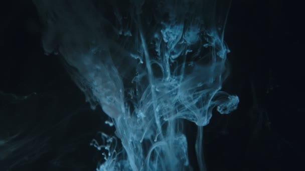 Pittura blu gocce miscelazione in acqua movimento lento. Inchiostro liscio che gira e schizza dallalto sottacqua. Inchiostro nuvola su sfondo nero.