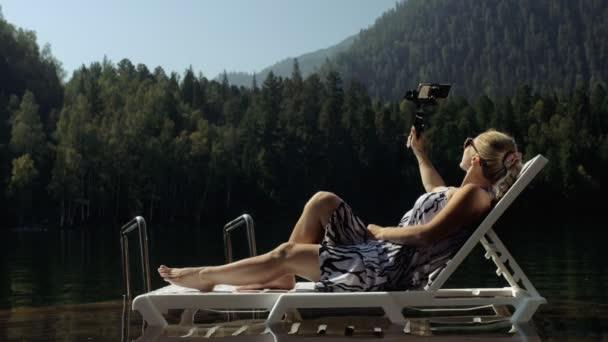 Frau dreht auf Handheld-Film-Gimbal-Stabilisierung für Smartphone. Mädchen liegen auf Pier und machen Selfie. Blogger überträgt Video-Vlogging.