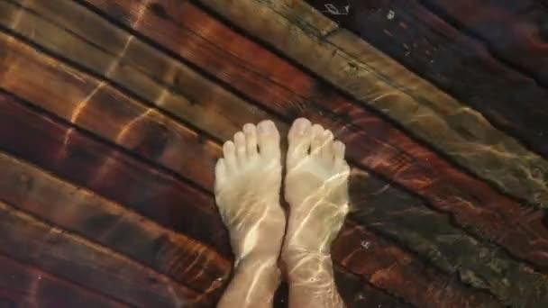 Meztelen, szőrös férfi lábak sétálnak a mólón. Egy férfi lába úszik. Az első ember. Az emberek a víz alatti mólón pihennek..