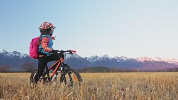 Jeden bělošský děti chodily pro kolo v pšeničné pole. Dívka, vycházkové černé oranžové cyklu na pozadí krásných zasněžených horách. Biker pohybu jezdit s batohem a helmu. Horské kolo tvrdý ocas.