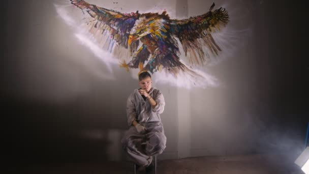 Artist designer draws an eagle on the wall. Craftsman decorator paints a picture with acrylic oil color. Vaper smokes vape.