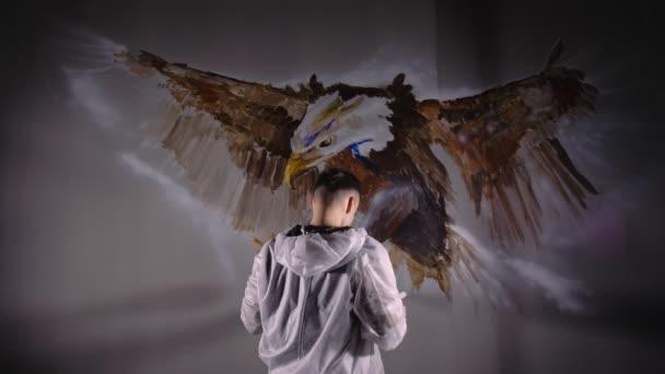 Umělec kreslí orla na zeď. Řemeslník dekoratér maluje obrázek akrylovou barvou oleje. Malíř malíř oblečený v plášti.
