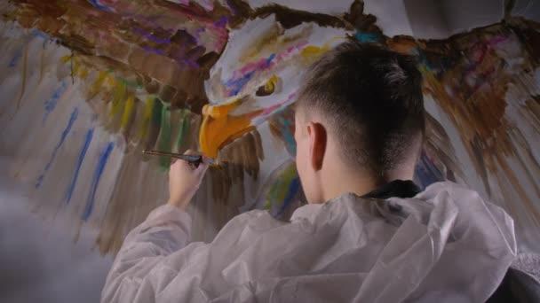 Künstler-Designer zeichnet einen Adler an die Wand. Handwerker Dekorateur malt ein Bild mit Acryl-Ölfarbe. Maler Maler im Anstrich.