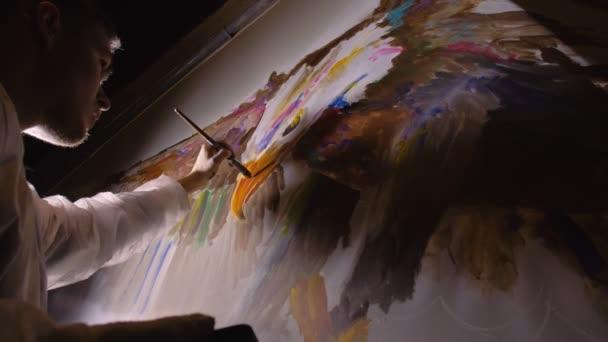 A művész tervező egy sast rajzol a falra. Kézműves dekorátor fest egy képet akril olaj színe nézi a vázlat a telefon.
