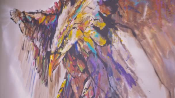 Artist designer draws an eagle on the wall. Craftsman decorator paints a picture with acrylic oil color. Painter painter dressed in a paint coat.