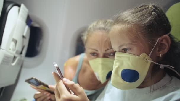Familie Frau und Kind reisen kaukasische Touristen im Flugzeug mit einer medizinischen Schutzmaske. Nutzen Sie Smartphone-Handys. Covid-19