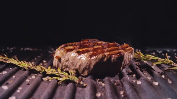 Lahodný šťavnatý masový steak na grilu. Smažené hovězí na elektrické pečeni, rozmarýn, černý pepř, sůl. Zpomalený pohyb.
