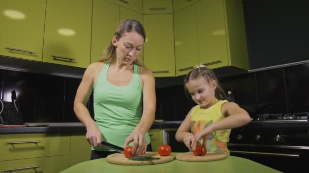 Mother teaching daughter smart girl learning to cook. Mistress children to cook a Neapolitan egg fried omelette from salame affumicato sausage.