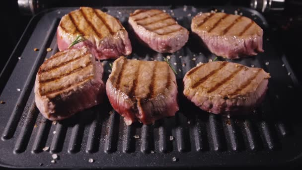 Lahodný šťavnatý masový steak na grilu. Prime hovězí smažené a nalít sůl, rozmarýn, černý pepř ve zpomaleném filmu.