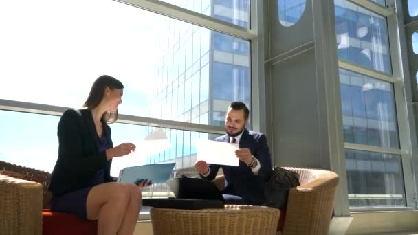 Two business people discussing documents
