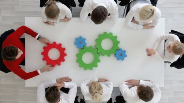 Business problem solution, mechanism of business, teamwork concept, business team sitting around white table with cogs