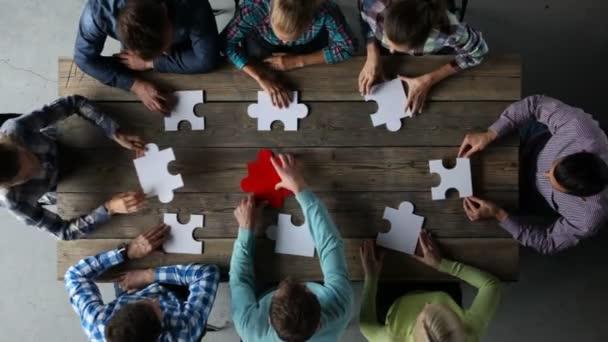Podnikatelé a puzzle na dřevěný stůl, týmové pojetí