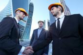 Architekti potřesení rukou na staveništi