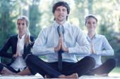 Geschäftsleute üben Yoga im Park