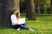Dospívající dívka pracující s přenosným počítačem v parku