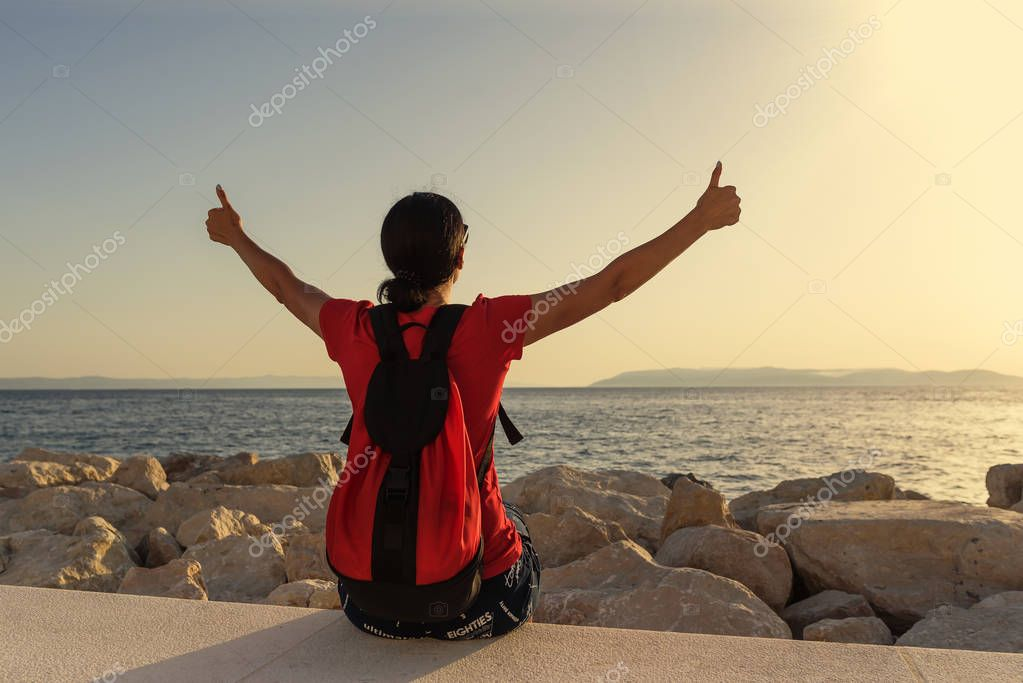 Young attractive woman showing thumbs up on hands sitting on the seashore.