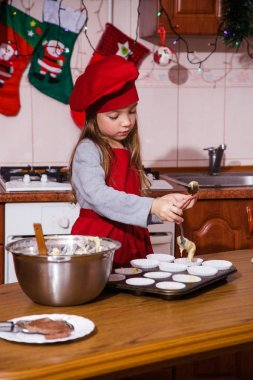 festive red apron Christmas party dinner dessert peppermint cupcakes cheese cream sugar sprinkling decoration girl new year red apron chef chief confectioner