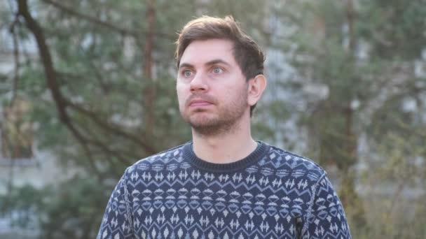 ulice muž mladý modrý oči zelené stromy přemýšlivý portrét jaro slunce štětiny