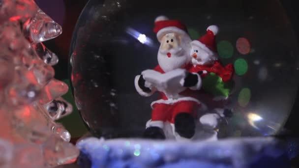 Mikulás közelében egy gyönyörű, színes, szilveszteri fenyő, ül egy üveg gömb, és előkészíti ajándékokat gyerekeknek az új évre