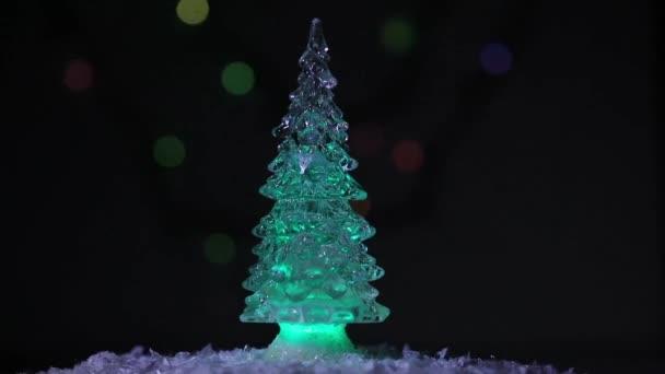 Vánoční jedle se otáčí na pozadí jasných, krásných a barevných ohňů