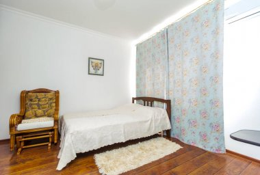 Sunny Room with a large double wooden bed, a rocking chair and a shaggy rug by the bed