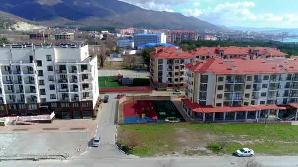 A newly built apartment complex consisting of several multi-storey buildings with red roofs. Video from the height of bird flight. The resort of Gelendzhik, the sea and the mountains..