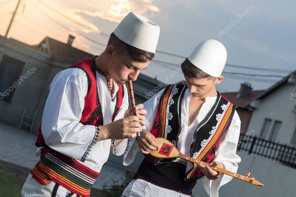teen boys in traditional albanian costume playing music with flu