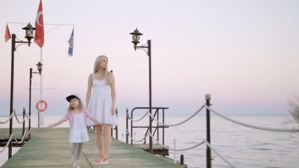 Matka a dcera chodí na dřevěné molo při západu slunce