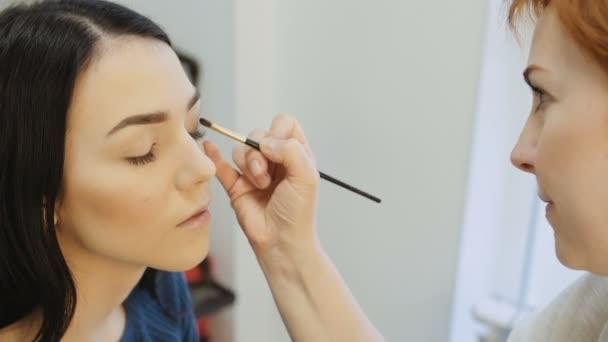 Close-up of a make-up artist applying make-up to the eyelash