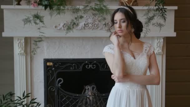 99eeabb3d3 Novia morena juguetona hermosa con vestido blanco posando en el fondo de la  chimenea– metraje de stock